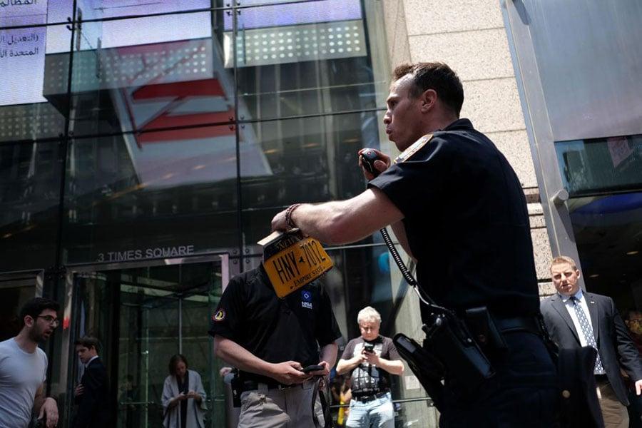 一名紐約警察撿起肇事車的車牌。(JEWEL SAMAD/AFP/Getty Images)