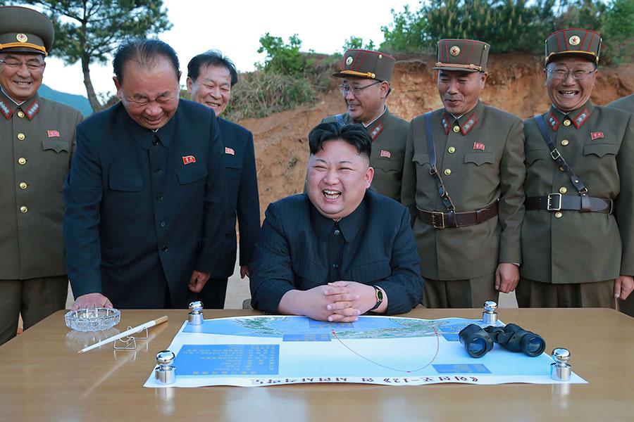 北韓於今年4個月內,選擇在北京召開兩次重要國際會議的當天,分別發射了一枚導彈和進行第六次核試。圖為全程觀看了導彈試射的北韓領導人金正恩(坐立者)。(STR/AFP/Getty Images)