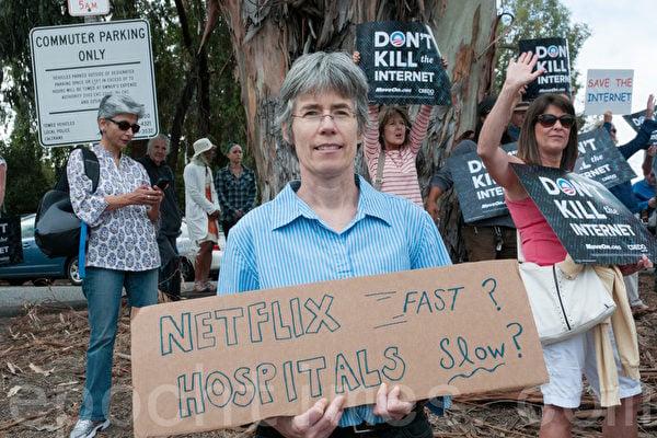 加州灣區居民瑪哈妮手持標語,支持「互聯網中立」。(屈婧/大紀元)