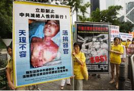 香港法輪功學員在呼籲制止中共迫害的遊行隊伍中,展示黑龍江法輪功學員王斌遭活摘器官的事實。(AFP)