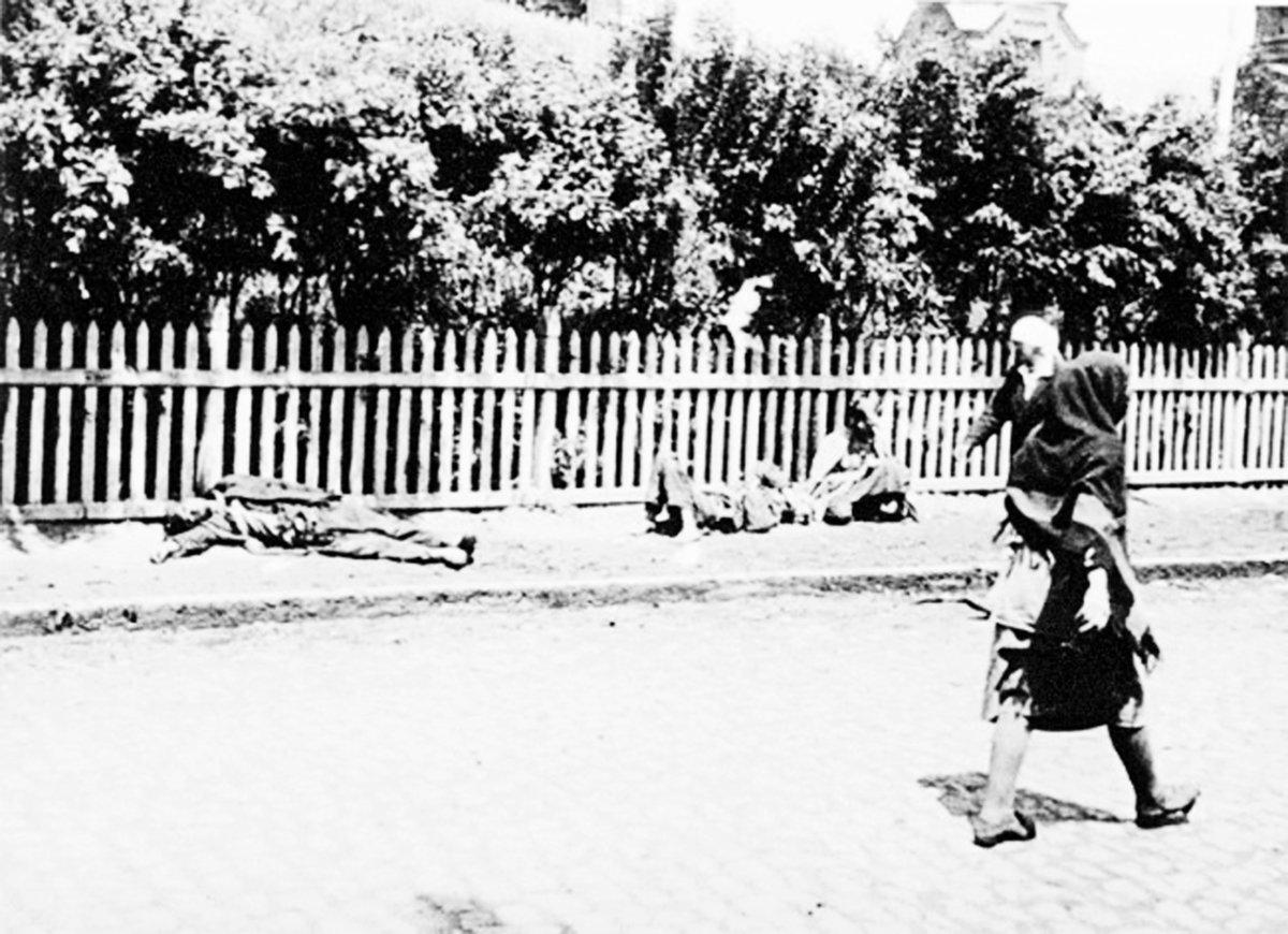 1933年蘇聯大饑荒期間,卡爾可夫的路人從餓殍前經過。(維基百科)
