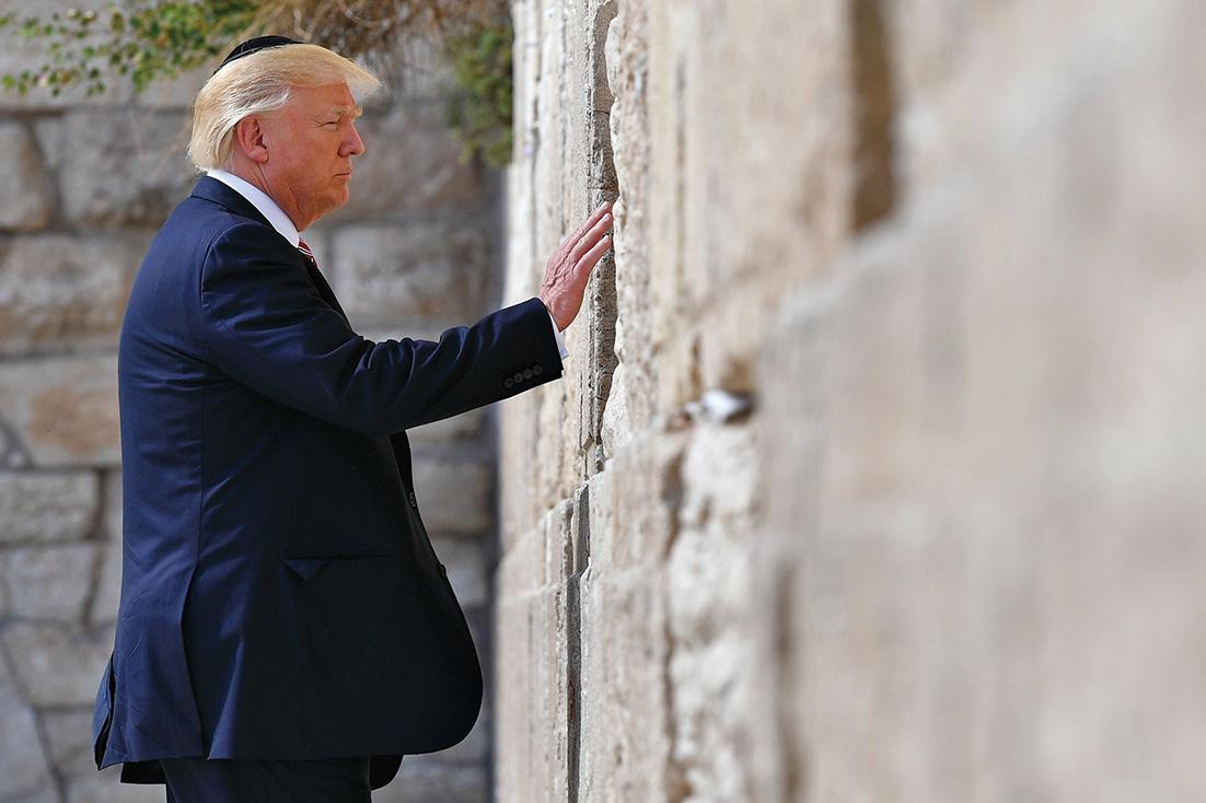 特朗普訪問耶路撒冷舊城的「哭牆」,將右手放在牆上,閉起眼睛祈禱約一分鐘,並依照慣例將一張「給上帝的紙條」塞在哭牆牆縫中。(AFP)