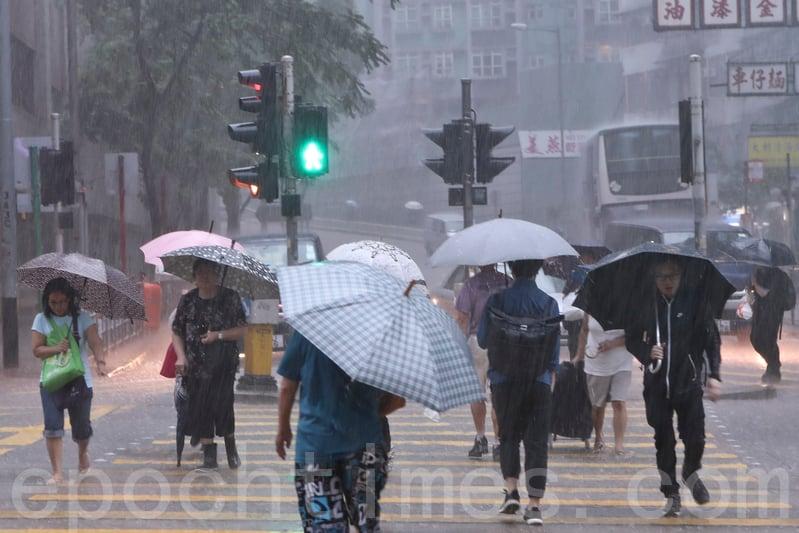 5月24日上午,香港天氣驟變,天文台在上午11時30分發出黑色暴雨警告信號。圖為暴雨下街上的途人。(余鋼/大紀元)
