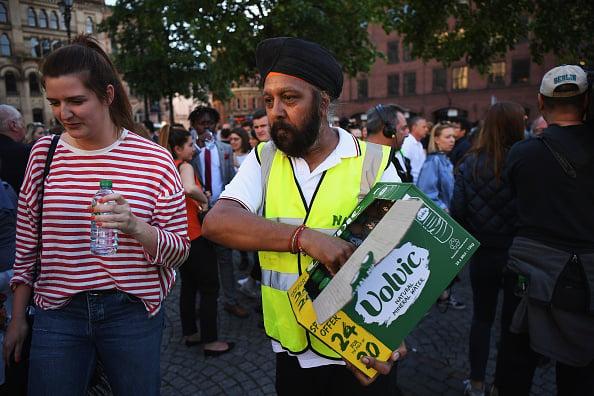 工作人員為參加燭光守夜的人提供免費的礦泉水。(Leon Neal/Getty Images)