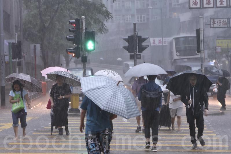 今早暴雨期間,市民需要冒雨上班上課。(余鋼/大紀元)