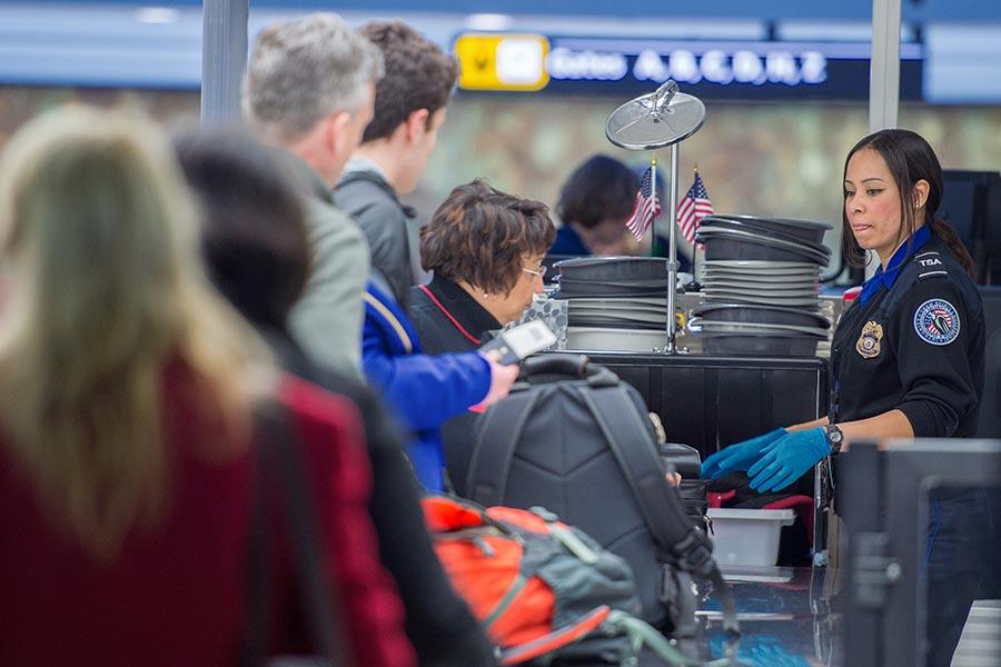 美國交通安全管理局(TSA)日前正在測試新的安檢措施,要求搭機乘客從包中取出任何大於手機的電子產品及食品,並對這些物品進行分別掃描。(PAUL J. RICHARDS/AFP/Getty Images)