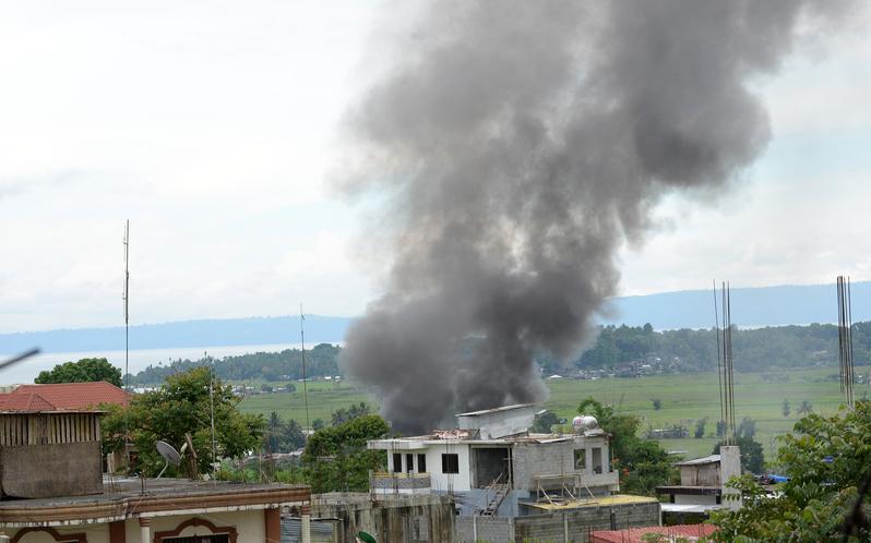 5月25日,菲律賓馬拉韋市陷入混亂,政府軍與恐怖份子作戰,市 集硝煙密布。(TED ALJIBE/AFP)