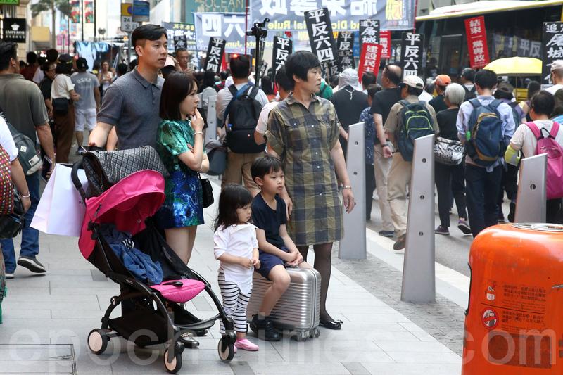 有遊客一家在馬路旁觀看六四遊行。(李逸/大紀元)