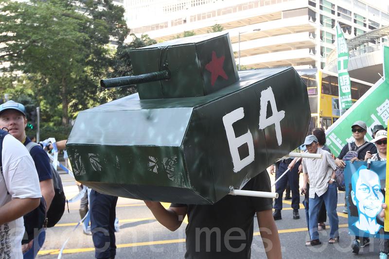 有市民戴上坦克車模型,諷刺中共在六四以坦克車鎮壓學生。(蔡雯文/大紀元)