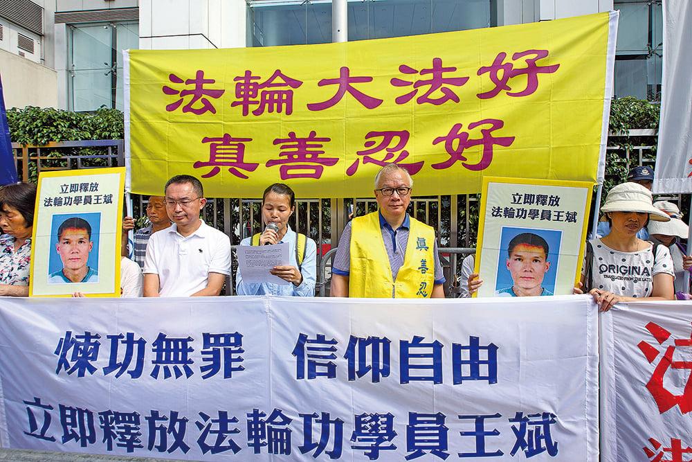 香港法輪功學員梁金友在江門的丈夫,也是學員的王斌遭當地公安綁架及非法關押。昨日下午,她聯同其他香港學員數十人,手持橫幅遊行到中聯辦抗議,呼籲各界協助,要求中共當局立即釋放王斌。(李逸/大紀元)
