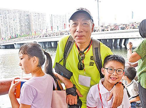 帶著小孫兒來觀看賽龍舟的張先生認為中國傳統文化非常重要,希望孫兒多了解這些活動。(童欣/大紀元)