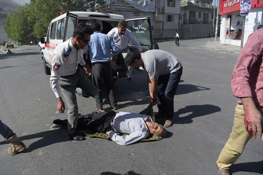 5月31日阿富汗首都喀布爾發生大爆炸事件,人們在救助傷者。(SHAH MARAI/AFP/Getty Images)