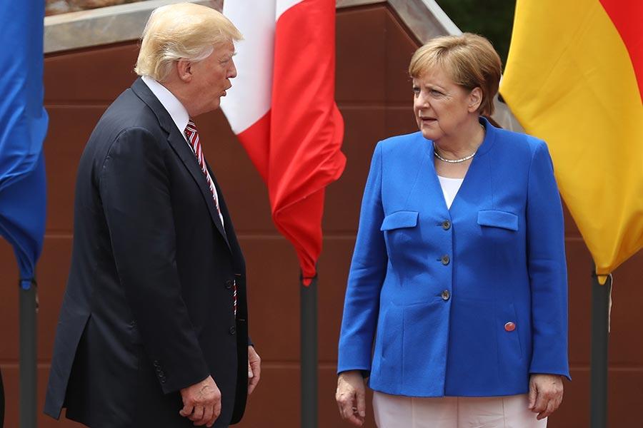 特朗普一旦決定退出巴黎氣候協議,美國的內政和外交上或將受到許多影響。圖為5月26日在意大利西西里島,特朗普和德國總理默克爾在G7峰會的與會者合影時交談。(Sean Gallup/Getty Images)