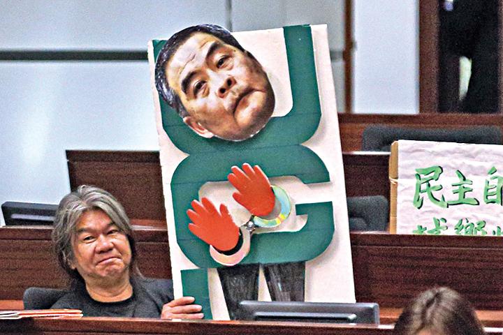 社民連議員梁國雄,以梁振英被鎖上手扣的紙牌道具諷刺UGL涉貪案。(李逸/大紀元)
