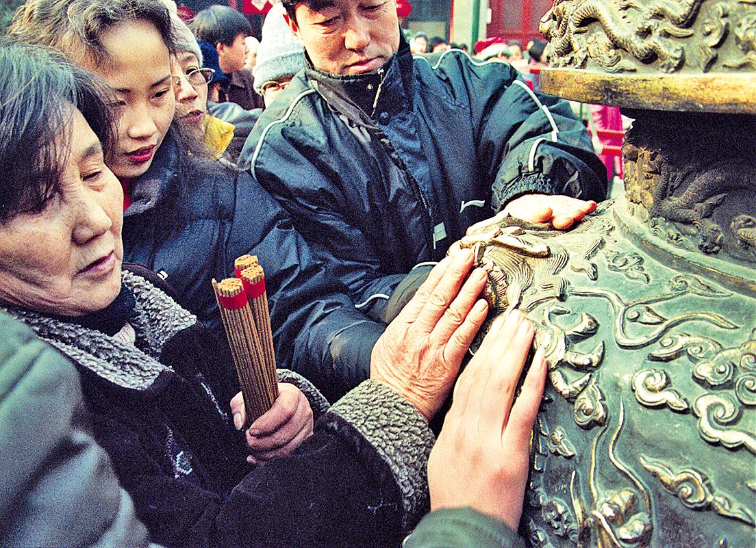 龍的圖騰深入中國生活。大年初一民眾觸摸廟宇香爐上龍紋求平安。(Newsmakers)