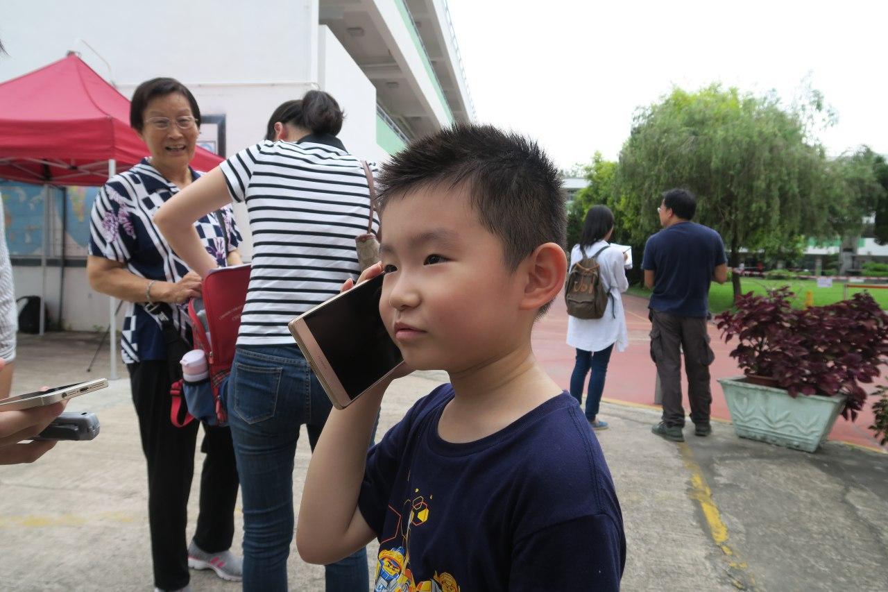 有獲派第一志願的小朋友打電話向家人報喜。(陳仲明/大紀元)