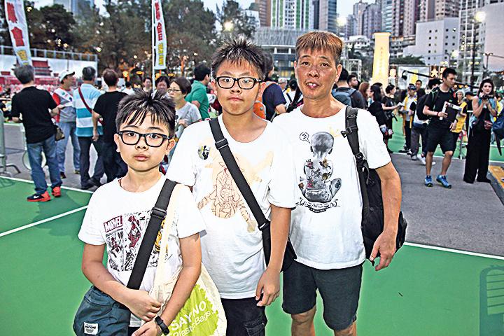 林先生(右)帶著孫兒——讀中一的林同學(中)及小五的顏同學(左)首次參與六四悼念。(李逸/大紀元)