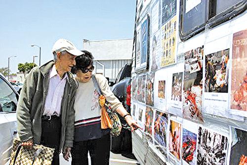 仔細閱讀中共暴行圖片的民眾張氏夫婦。(徐綉惠/大紀元)