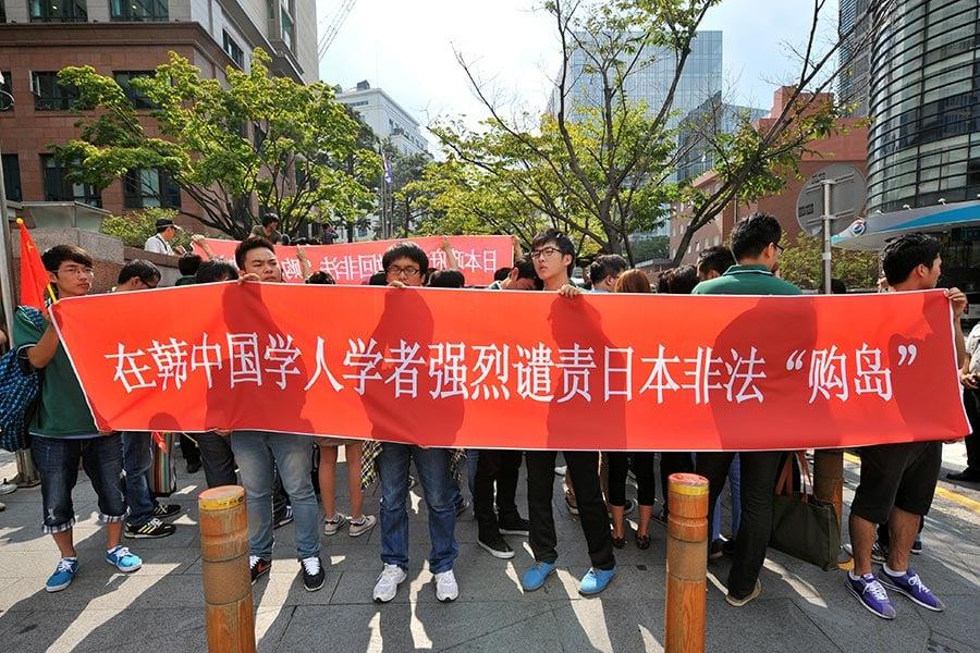 中國學生學者聯誼會不僅遏制自由言論,而且規定「正確的言行」。比如CSSA組織人群歡迎中共總理李克強訪問澳洲、抗議達賴喇嘛在加州大學演講、反對哥倫比亞大學的人權演講。 圖為在南韓的中國學生會舉行抗議活動。(JUNG YEON-JE/AFP/Getty Images)