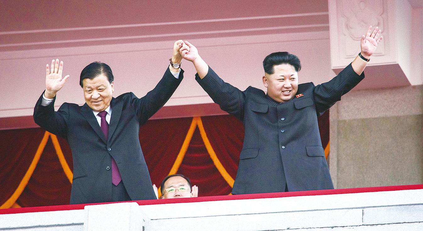 2015年10月10日,北韓舉行閱兵儀式,慶祝勞動黨建黨70周年,到訪平壤的中共中央政治局常委劉雲山和北韓最高領導金正恩一起觀看閱兵儀式。 (ED JONES/AFP/Getty Images)