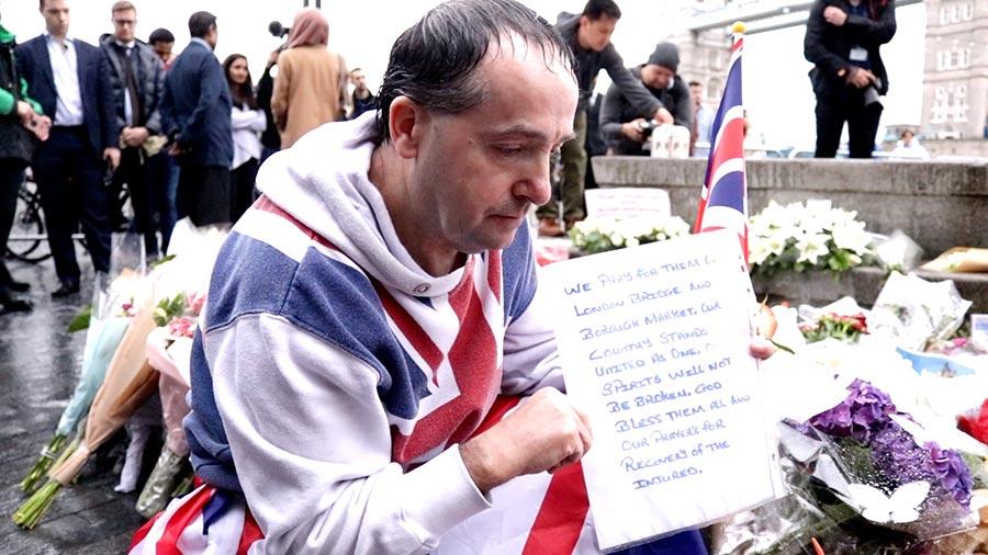 一位身穿英國國旗套頭衫的先生蹲在鮮花邊,手裏舉著自己寫的悼念詞,長時間在淅瀝細雨中堅守著。(任真/大紀元)