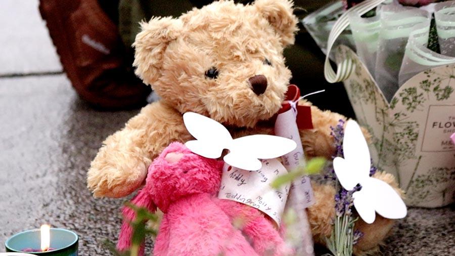 在民眾獻上的一束束鮮花中,一個絨毛玩具熊和一個玩具兔子很引人注目。(任真/大紀元)