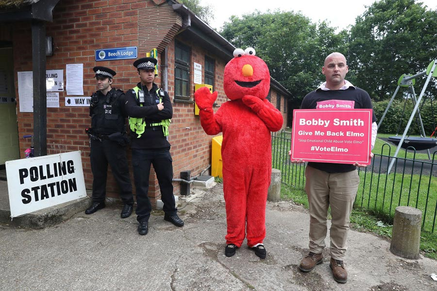 MAIDENHEAD, ENGLAND - JUNE 08: Candidate Bobby Smith arrives with Elmo as Police wait outside the polling station where Conservative Party leader Theresa May is expected to vote on June 8, 2017 in Maidenhead, England. Polling stations have opened as the nation votes to decide the next UK government in a general election. (Matt Cardy/Getty Images)