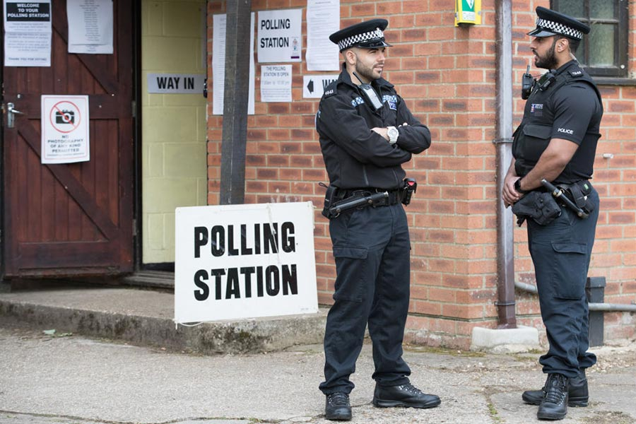 MAIDENHEAD, ENGLAND - JUNE 08: Police officers stands outside the polling station in Sonning Guide & Scout hut after casting their vote on June 8, 2017 in Sonning near Maidenhead, England. Polling stations have opened as the nation votes to decide the next UK government in a general election. (Matt Cardy/Getty Images)