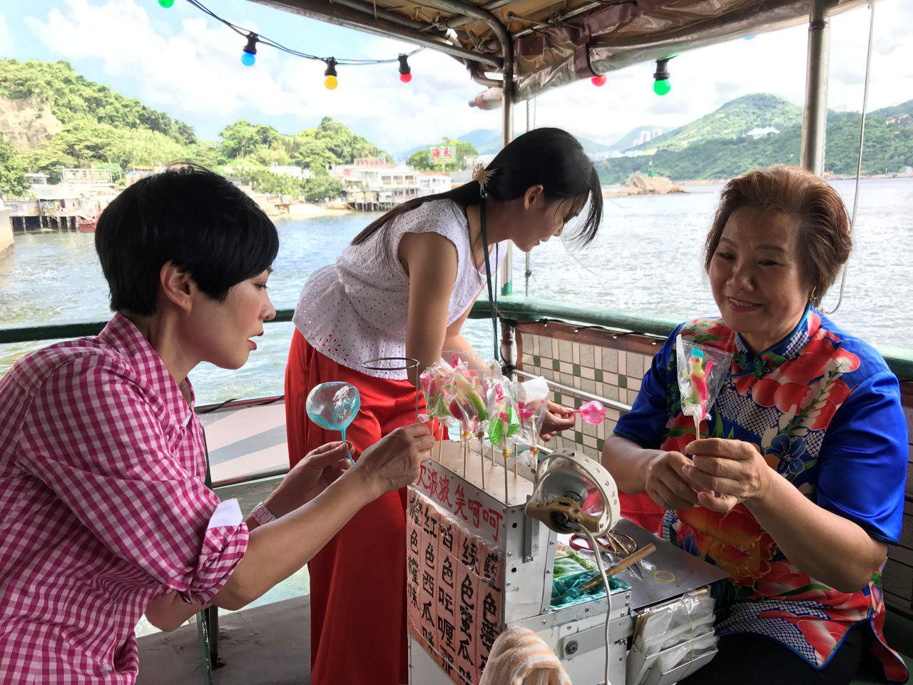 譚玉瑛很認真的聽糖姨教導如何吹波波糖。(王文君/大紀元)
