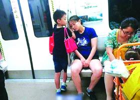 小男孩地鐵讓座 用手為媽媽墊著睡覺