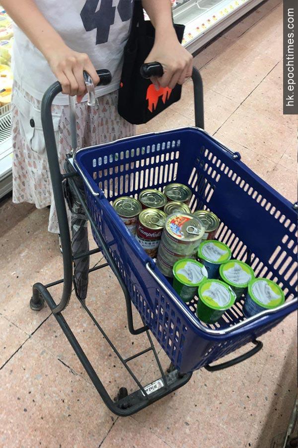 有市民購置大量罐裝食物、乳酪等。(盛益清/大紀元)
