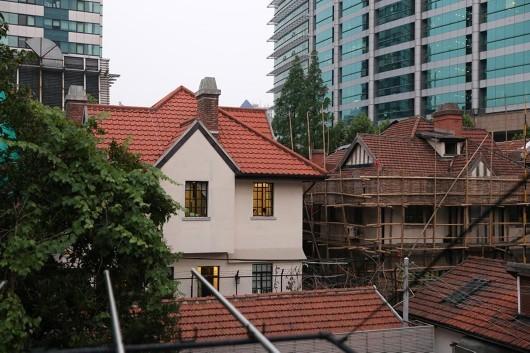 毗鄰涉事建築西側的房屋,展現了巨鹿路888號附近老式建築群的風貌(畫面右側房屋是正常維修)。(網絡圖片)