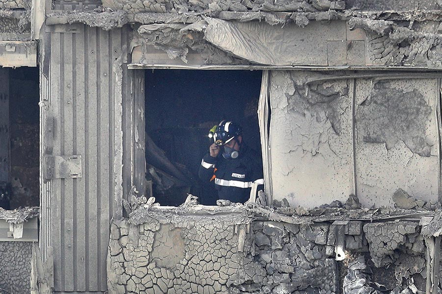大火過後,消防隊員在檢查建築物內部。(Dan Kitwood/Getty Images)