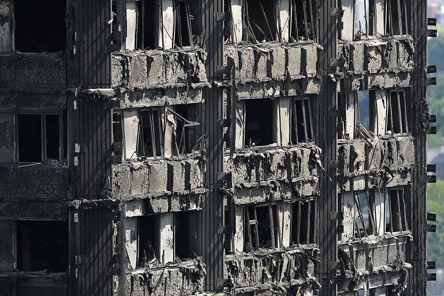 16日下午,幾百名遇難者家屬及生還者在當地市政廳外抗議,數十名示威者一度衝進市政廳。抗議者質疑「人為因素」造成火災。圖為被燒焦的倫敦格蘭菲塔樓。(Dan Kitwood/Getty Images)