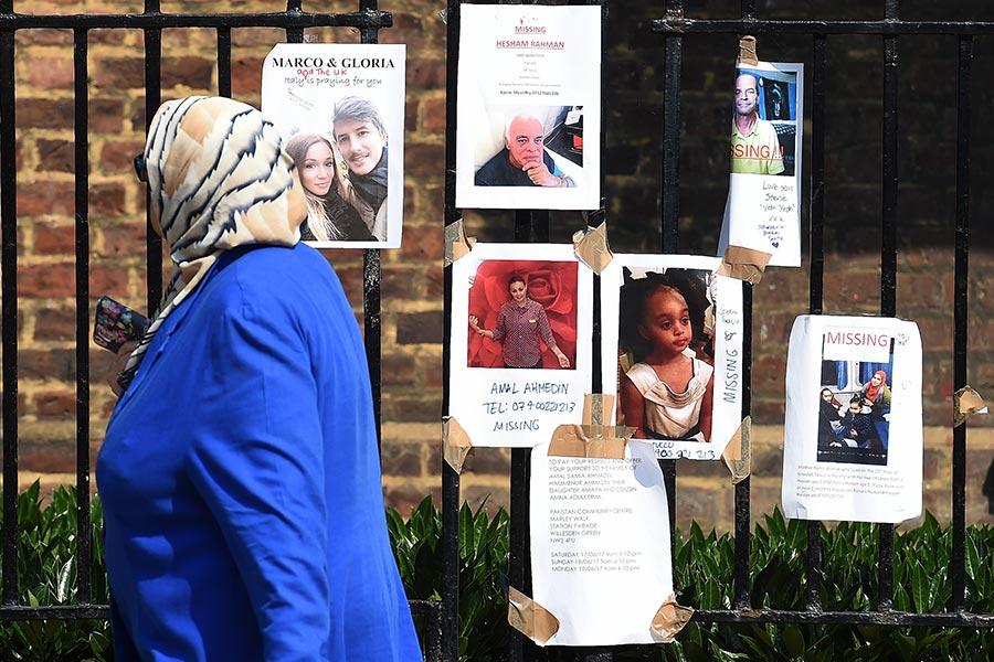 倫敦警務處今日表示,格倫費爾大廈的死亡或失蹤人數已增至79人,而較早前有5名失蹤人士,現已證實他們安全。圖為張貼出來的失蹤者照片。(PAUL ELLIS/AFP/Getty Images)