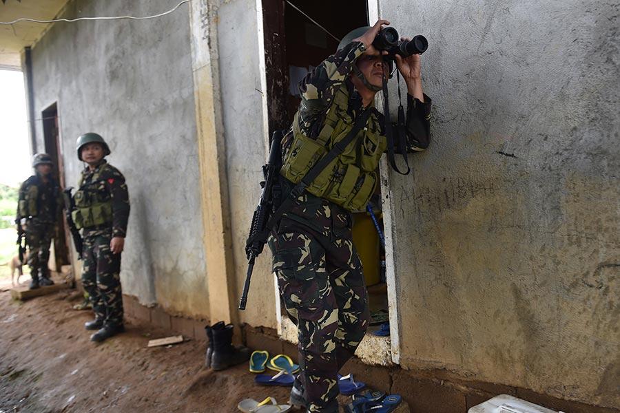 2017年6月20日,菲律賓政府軍在南部的馬拉威市,對當地受伊斯蘭國極端組織支持的武裝組織展開新一輪的強勢攻擊,希望能在本周齋戒月結束前平定當地已一個多月的戰亂。本圖為19日地面步兵隊在市區大樓進行搜索與清除任務。(TED ALJIBE/AFP/Getty Images)