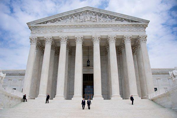 美國最高法院首席大法官羅伯茨(中間靠右者)和大法官戈薩奇(中間靠左)6月15日走下高院台階。(JIM WATSON/AFP/Getty Images)