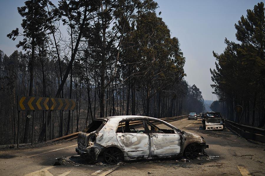 圖為葡萄牙一條公路上被森林大火波及的汽車。(PATRICIA DE MELO MOREIRA/AFP/Getty Images)