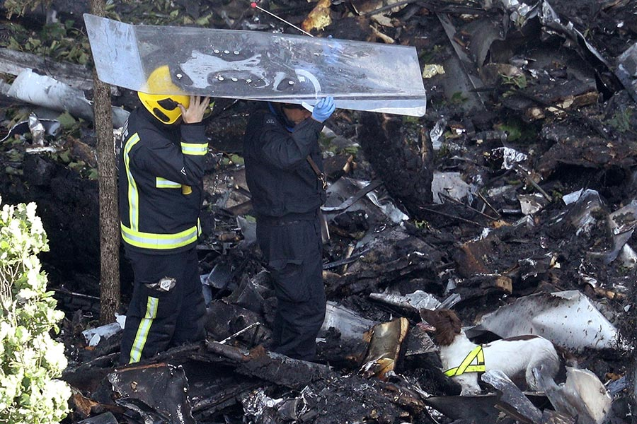 消防員和嗅探犬於6月15日在倫敦格倫費爾大廈下檢查碎片,消防員頭頂鋼化玻璃板,以防被上面掉下來的東西砸到。(Dan Kitwood/Getty Images)