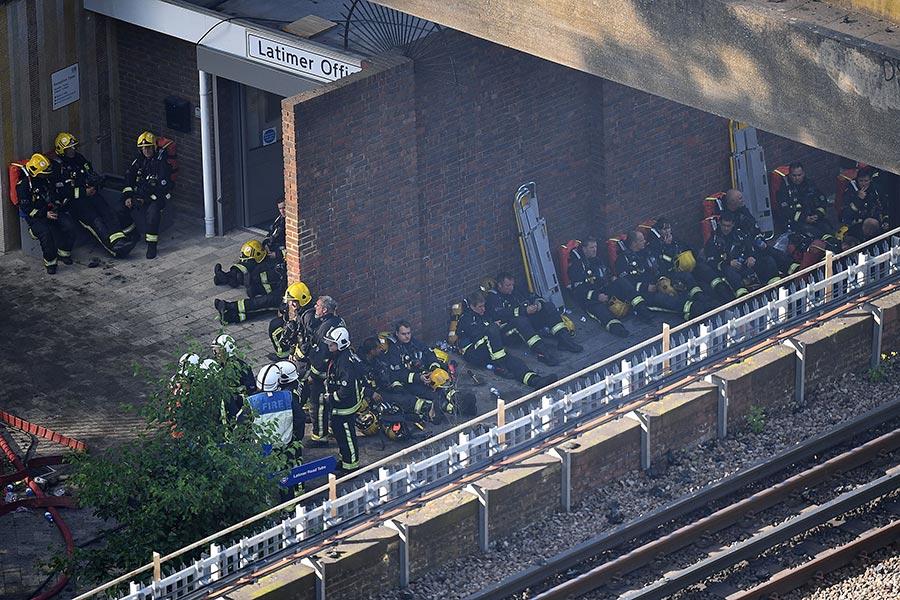 6月14日凌晨,倫敦24層的住宅樓格倫費爾大廈陷入一片火海之中,超過200名消防員到現場滅火救人。圖為當天白天精疲力盡的消防員在塔樓附近休息,等待著進入大樓開展下一輪的救人行動。(Leon Neal/Getty Images)
