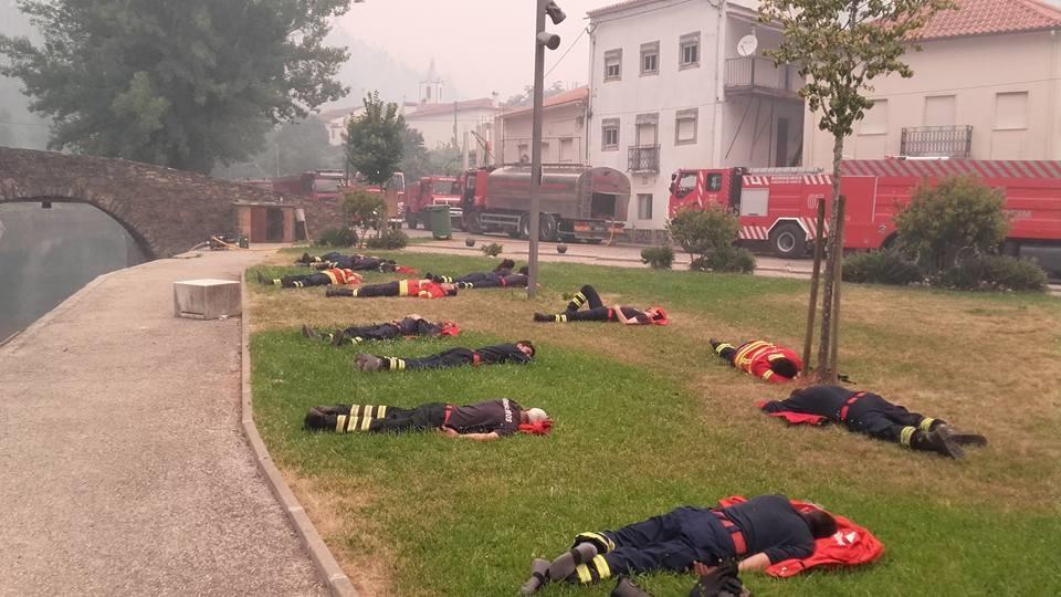 葡萄牙森林大火救災現場,13名精疲力竭的消防員好不容易可以躺在草坪上休息片刻。(Pedro Brás/Facebook)