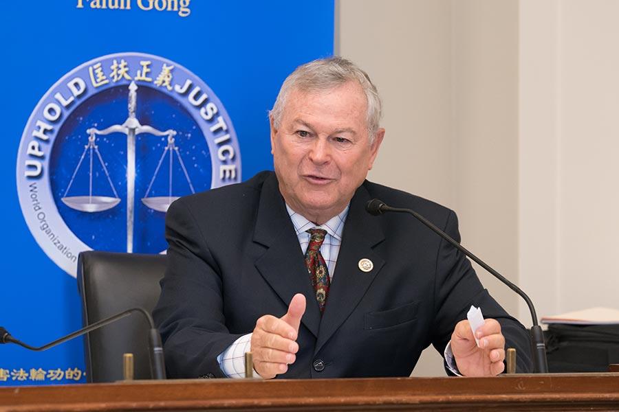 「追查國際」主席汪志遠(中)向美國議員(右)遞交調查報告。(石青雲/大紀元)