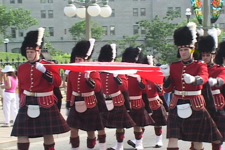 英國衛隊的註冊商標大禮帽,這種熊皮禮帽已有200年傳統。圖為去年7月1日加拿大國慶慶典遊行——8名持國旗的皇家衛隊士兵。(大紀元)
