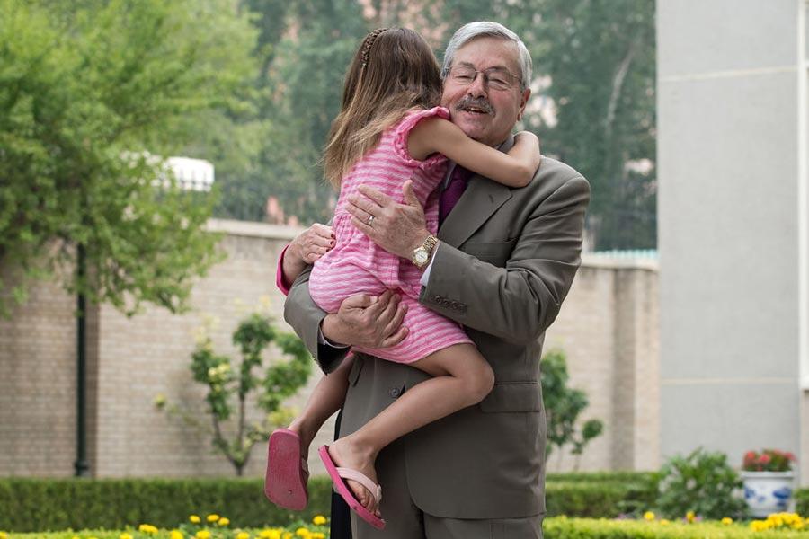 6月28日,美國駐華大使全家在北京跟媒體見面,6歲的外孫女索菲亞趴在外公的懷裡。(NICOLAS ASFOURI/AFP/Getty Images)
