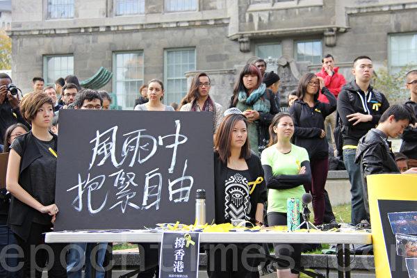 2014年,加拿大麥吉爾大學(McGill University)的學生們舉著「風雨中抱緊自由」的牌子支持香港學生。(鍾原/大紀元)
