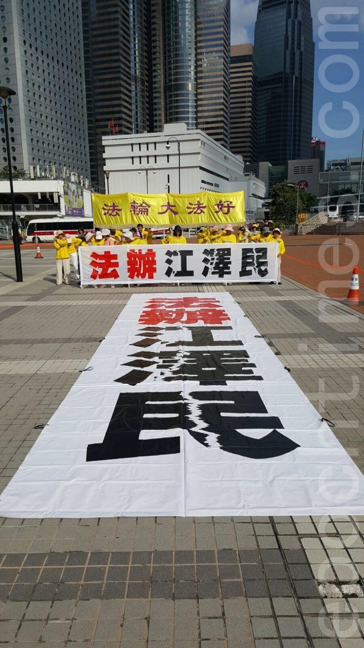 香港部份法輪功學員,早上在愛丁堡廣場集體煉功,遙向習近平下榻的海景萬麗酒店,打出「法辦江澤民」的巨型橫幅。(林怡/大紀元)