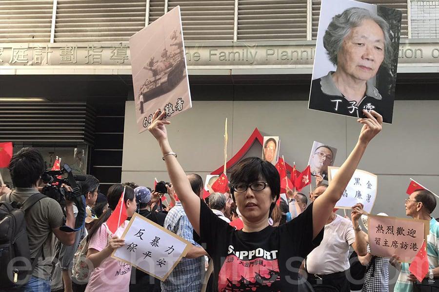 支聯會下午5時半從在灣仔「家計會」前空地,準備遊行至電訊大廈。但一批揮舞著紅色旗幟的親共組織成員突然一擁而上包圍,並試圖用紅旗遮擋支聯會的抗議標語。(李逸/大紀元)