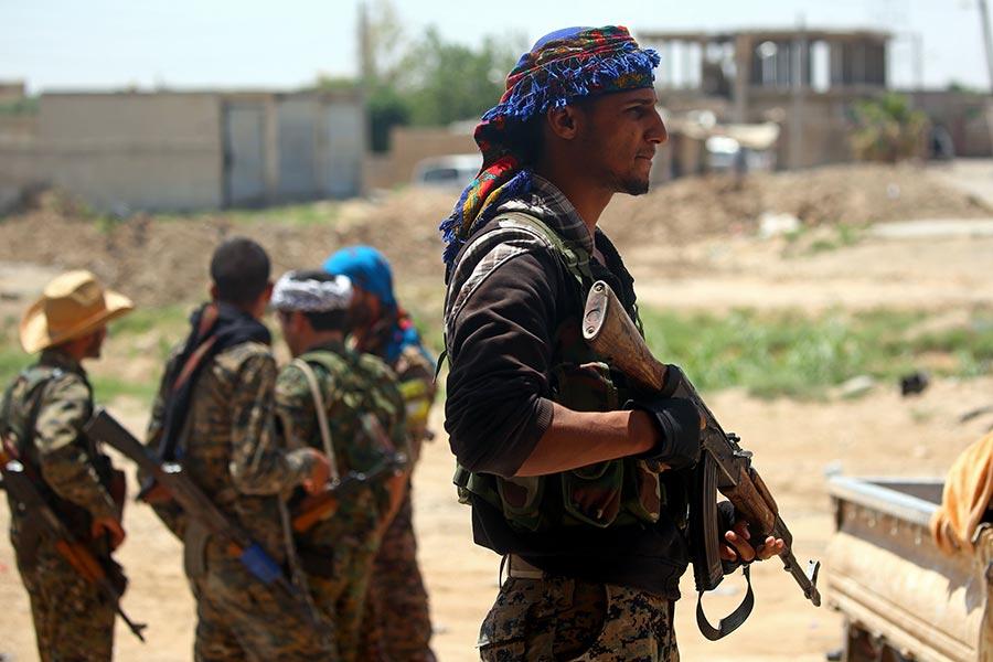 由美國支持的敘利亞民主力量聯合部隊已從水陸全面包圍北部城市拉卡,即將開始圍捕伊斯蘭國極端組織仍在該地頑強抵抗的殘餘的2,500名成員。本圖為進入拉卡市的敘利亞民主力量聯合部隊士兵。(DELIL SOULEIMAN/AFP/Getty Images)