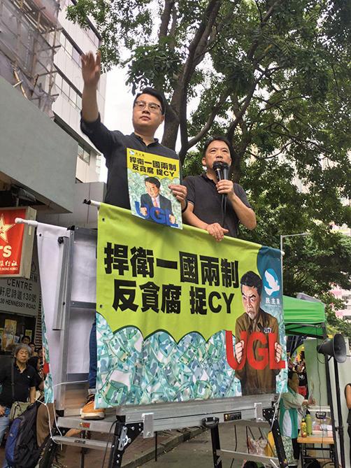 7月1日香港七一大遊行,民主黨的街站掛出「反貪腐、捉CY」漫畫,畫中梁振英身穿囚衣、手上戴著「UGL手銬」。(黃瑞秋/大紀元)
