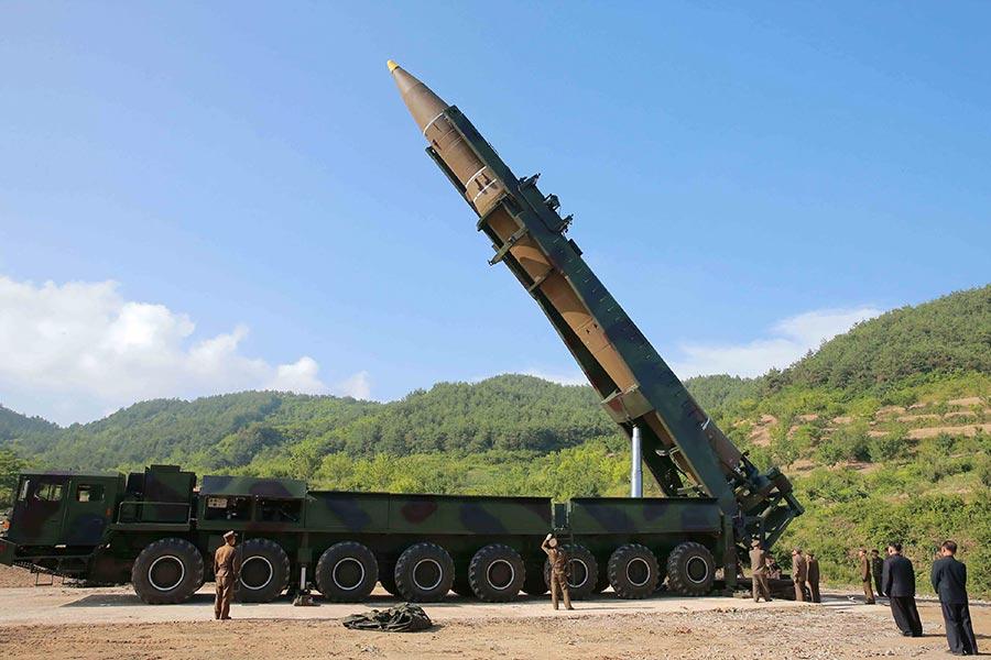 北韓在當地時間周二(7月4日)清晨試射一枚彈道導彈,而其用來運送導彈的車輛,似為中國大陸生產的卡車。圖為韓國民眾觀看北韓試射首枚洲際導彈的報道。(STR/AFP/Getty Images)